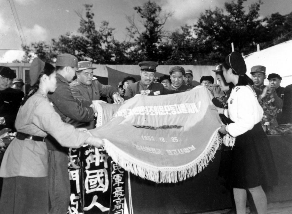 1953年10月,中国人民志愿军参谋长李达(左五)陪同中国人民第三届赴朝慰问团总团长贺龙(左四)与朝鲜人民军最高司令部互赠锦旗。