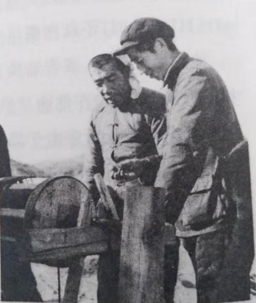 陈永贵在虎头山的一个旱井提土架旁,看着王银虎手拿一把黄土讲解旱井治漏法。