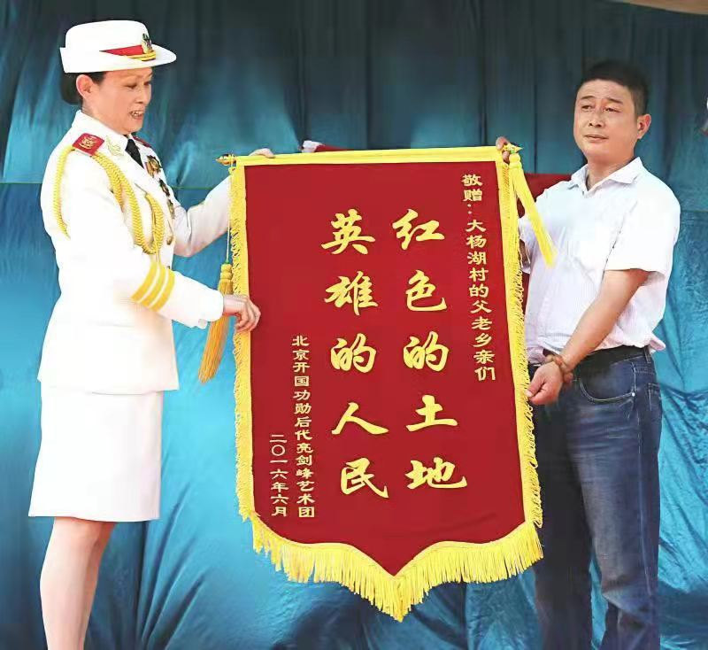 2016年,王媛媛代表开国功勋后代亮剑峰艺术团向大杨湖村赠送锦旗。
